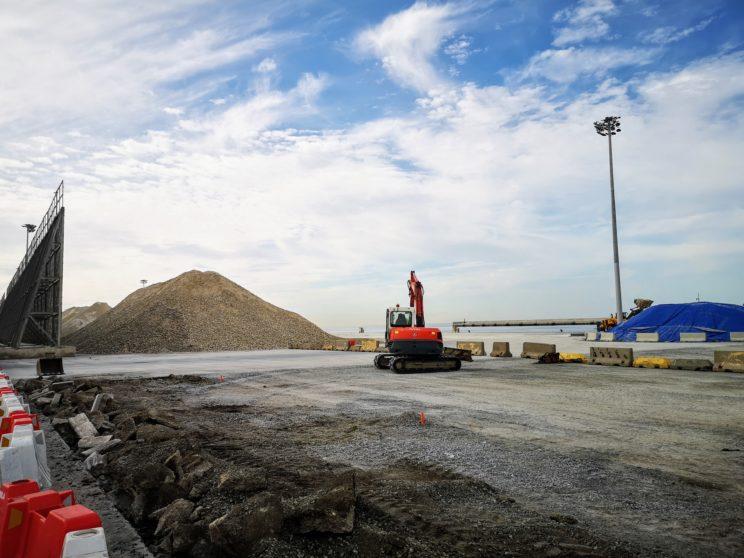 Una excavadora trabaja en la zona donde se levantarán las nuevas pantallas atrapa-polvo, en el Muelle de Pechina